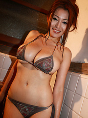 Sizzling asian hottie soaps up her giant plump tits in a bikini - Pics
