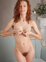 Dennie strips on the couch baring her petite body and unshaven pussy. - Pics