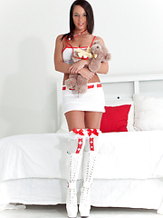 Sexy nurse in white-and-red stockings and high white boots