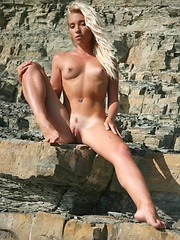 Breathtaking view of a nude blonde with carefree poses amidst the steep, rocky terrain. - Pics
