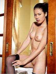 Jackie looks ravishing in sheer black thigh-high stockings, with her black hair tied high in a ponytail as she strike a variety of breathtakingly erotic poses by the bed. - Pics