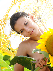 Suzanna A's carefree allure and charming beauty stands out amidst a field of sunflowers