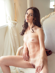 Magali playfully lifts up the hem of her dress until her humble yet delightfully puffy breasts and shaved pussy come into full view. - Pics