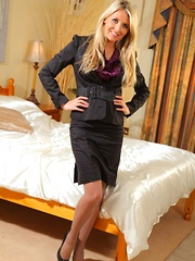 Stunning secretary wearing a black skirt suit and satin blouse.